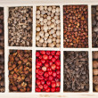 Assortment of different peppercorns in wooden box — Stock Photo
