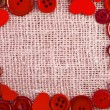 Border frame of red buttons and hearts on canvas burlap background texture — 图库照片