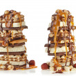 Chocolate and caramel syrup poured on stack of chocolate pieces on white background — Stock Photo