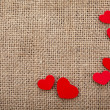 Stock Photo: Valentine's day card with wooden red hearts symbol on fabric sack texture background