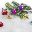 Christmas colorful balls and fir branch on white snow background - Stockfoto