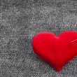 Valentine's day red heart symbol with needle on jeans texture background - 图库照片