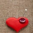Valentine's day red heart symbol with needle on fabric sack texture background - Stock Photo