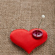 Valentine's day red heart symbol with needle on fabric sack texture background - Stockfoto