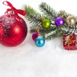 Christmas colorful balls and fir branch on white snow background — Стоковая фотография