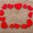 Valentine's day card with wooden red hearts symbol on fabric sack texture background - Foto Stock