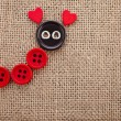 Valentine's day card with wooden red hearts buttons symbol on fabric sack texture background - Stok fotoğraf
