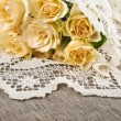 Wedding card with bunch of cream roses on burlap canvas texture with retro crochet doily — Stock Photo #21191171
