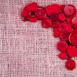 Border of red buttons and hearts on canvas burlap background texture — 图库照片