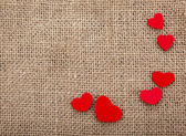 Valentine's day card with wooden red hearts symbol on fabric sack texture background — Foto Stock