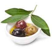Gemengde ingemaakte olijven met verschillende soorten olijven in een kom op een witte achtergrond — Stockfoto