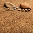 Pair trace feet made of a pebble stone on the sea sand desert texture backdrop — Stock Photo #23529073