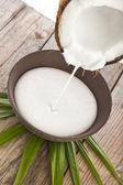 Noix de coco fêlé avec éclaboussures de lait dans une table en bois blanc — Photo