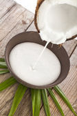 Cracked coconut with milk splash in wooden table on white — Stock Photo