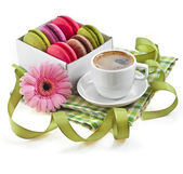 Coffee cup with colorful macaroons in a table serviette on a white background — Stock Photo