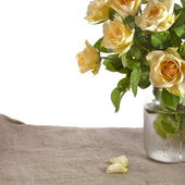 Bouquet of cream tea roses on canvas cloth texture with copy space for text isolated on white background — Stock Photo