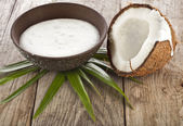 Craquage noix de coco avec la crème de lait dans un bol en argile sur table en bois — Photo