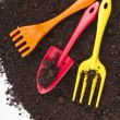 Stock Photo: Colorful gardening tools in soil surface corner border
