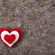 Heart symbol on wool felt texture - Stock Photo