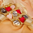 Sweet Marzipan heart candy on golden silk textured cloth card background - Stock Photo