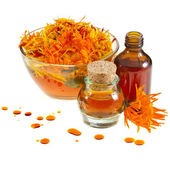 Herbal calendula in the glass and aromatherapy essential oil — Stock Photo