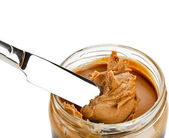 Glass with peanut butter creamy and knife — Stock Photo