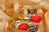 Chocolate and marchpane hearts candies on golden silk — Stock Photo