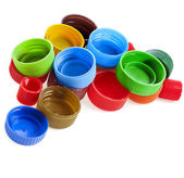 Bunch of multicolored used plastic bottle caps on white background — Stock Photo