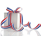 Gift box wrapped striped red blue ribbon tape isolated on white background — Stock Photo