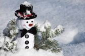 Happy Christmas snowman sitting in a snowy winter conifer fir tree — Stock Photo