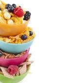 Confine di fiocchi di mais in una ciotola di plastica colorata con bacche fresche isolato su sfondo bianco — Foto Stock