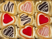 Chocolate and marzipan hearts candies on golden textured background — Stock Photo