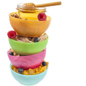 Tower stack of colorful plastic bowl with fresh berries and corn flakes isolated on white background — Stock Photo
