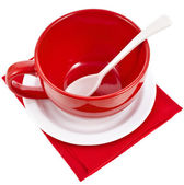 Red cup with spoon on white table napkins isolated on white background — Stock Photo