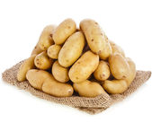 Raw potatoes heap with sack cloth isolated on a white background — Stock Photo