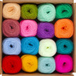 Multicolored balls of wool knitting yarn in a cardboard box on white background — Stock Photo