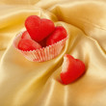 sladké červené marcipán srdce cukroví na povrchu pozadí zlaté hedvábné tkaniny — Stock fotografie #31699993