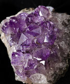 Natural cluster of Amethyst surface close up against a black background — Stock Photo