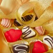 Chocolate and marchpane hearts candies on golden silk textured cloth background — Foto Stock
