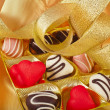 Chocolate and marchpane hearts candies on golden silk textured cloth background — Stockfoto