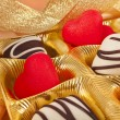 Chocolate and marchpane hearts candies on golden silk textured cloth background — Stock Photo