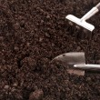 Close up of organic soil surface background with gardening tool — Stock Photo