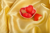 Sweet Red Marzipan heart candy on golden silk cloth surface background — Stock Photo