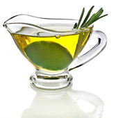 Olive oil sauce with rosemary herbs in the in gravy boat isolated on white background — Stock Photo