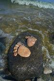 Två spår fötter gjorda av en sten sten på sea wave bakgrund — Stockfoto