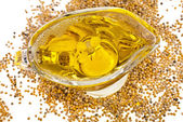 Mustard Oil in gravy boat and heap seeds — Stock Photo