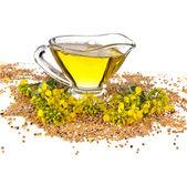 Flower Oil in gravy boat and mustard flower — Stock Photo