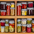 Many glass bottles with preserved food in wooden cabinet Isolated on white background — Stock Photo