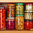 Many glass bottles with preserved food in wooden cabinet Isolated on white background — Stock Photo #36634991