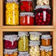 Many glass bottles with preserved food in wooden cabinet Isolated on white background — Stock Photo #36635607